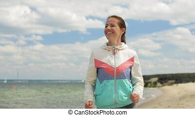 smiling woman running along beach - fitness, sport and...