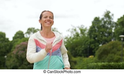 smiling woman running along park - fitness, sport and...