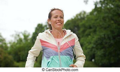 woman with earphones running at park - fitness, sport and...