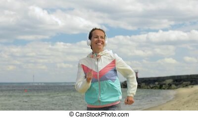 smiling woman with headphones running along beach - fitness,...