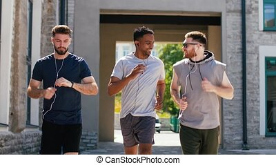 male friends with earphones running outdoors - fitness, ...