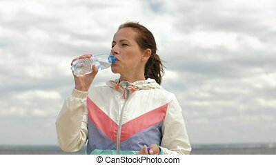 woman drinking water after exercising on beach - fitness,...