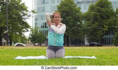 woman exercising on yoga mat at park - fitness, sport and...