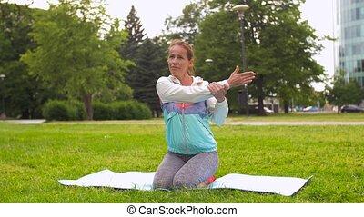 woman exercising on yoga mat at park