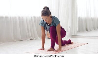 woman making high lunge exercise at yoga studio - fitness,...