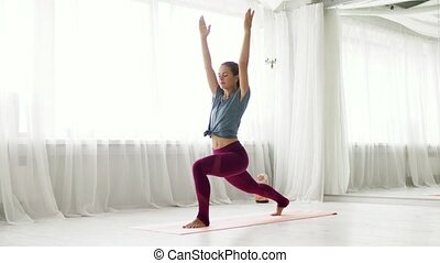 woman making high lunge exercise at yoga studio - fitness, ...
