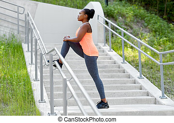 young african american woman stretching outdoors