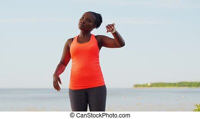 fitness, sport and healthy lifestyle concept - young african american woman stretching outdoors