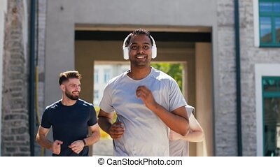 male friends with headphones running outdoors - fitness,...