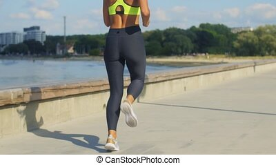 young woman in headphones running outdoors - fitness, sport ...