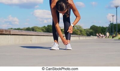 woman tightening sneakers and running outdoors - fitness, ...