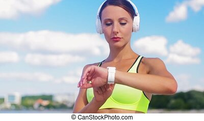 woman with headphones and smart watch running - fitness, ...