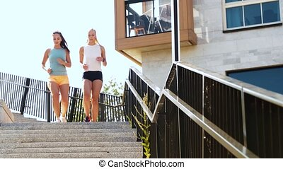 young women or female friends running downstairs - fitness,...