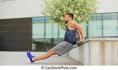 fitness, sport and training concept - young man doing triceps dip on city street