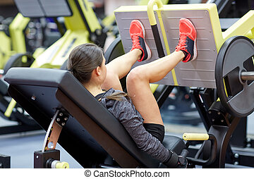 woman flexing muscles on leg press machine in gym - fitness...