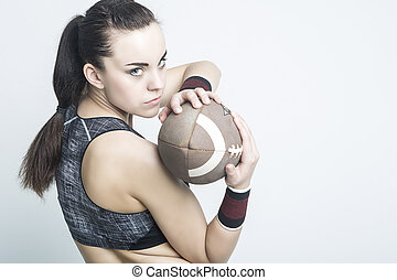 Fitness, Sport Concepts and Ideas. Sportive Caucasian American Football Female Player Athlete Posing with Ball. Looking Backwards