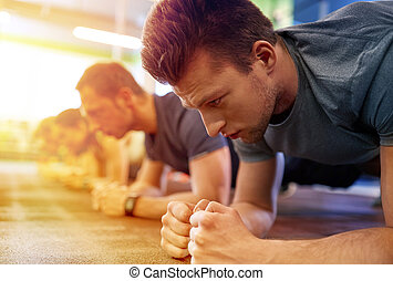 man doing plank exercise at group training in gym