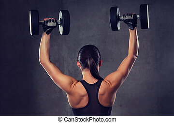 young woman flexing muscles with dumbbells in gym - fitness...