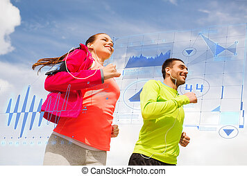 smiling couple with earphones running outdoors - fitness, ...