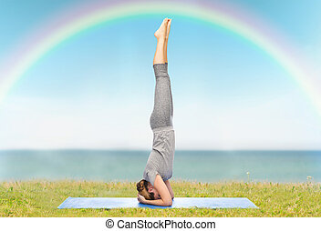 fitness, sport, people and healthy lifestyle concept - woman making yoga in headstand pose on mat over blue sky, rainbow and sea background
