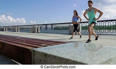 Fitness, sport, people, exercising and lifestyle concept - couple doing squats on city street