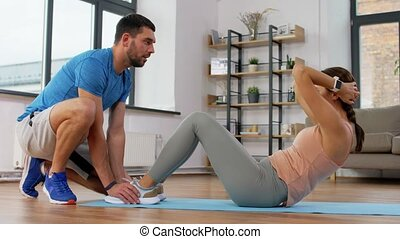 woman with personal trainer doing sit ups at home - fitness...