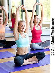 group of smiling women stretching in gym - fitness, sport, ...