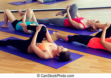 group of women stretching in gym - fitness, sport, training ...