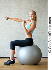 smiling woman with dumbbells and exercise ball
