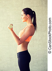 smiling woman with dumbbells in gym