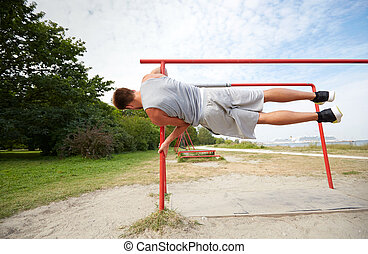 young man exercising on parallel bars outdoors - fitness, ...