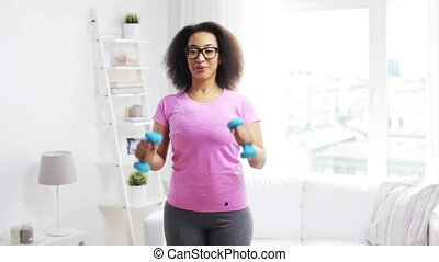 african woman exercising with dumbbells at home