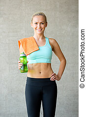 woman with bottle of water in gym