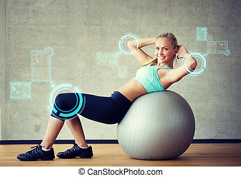 smiling woman with exercise ball in gym