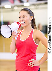 beautiful sporty woman with megaphone at gym - fitness,...