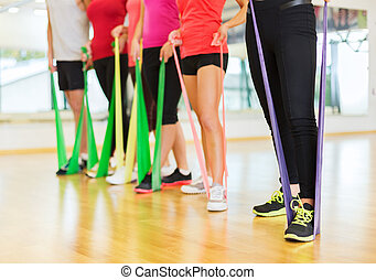 group of people with working out with rubber bands -...