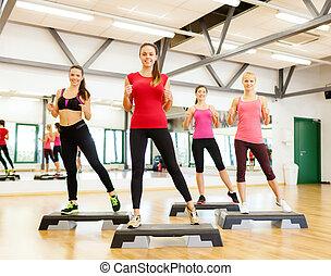 group of smiling female doing aerobics