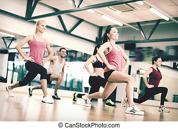 group of smiling people exercising in the gym - fitness, ...