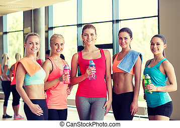 group of women with bottles of water in gym