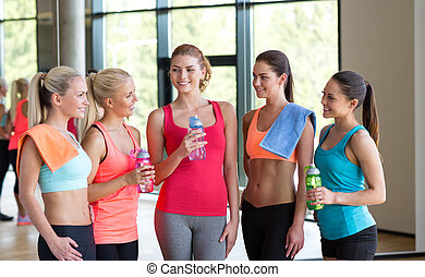 women with bottles of water in gym