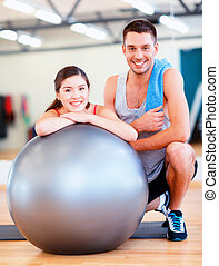 two smiling people with fitness ball