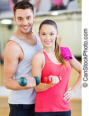 two smiling people working out with dumbbells