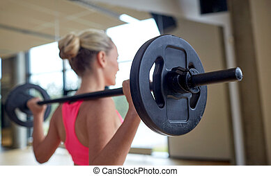 happy woman flexing muscles with barbell in gym - fitness, ...