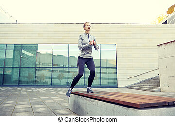 woman making step exercise on city street bench