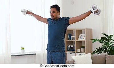 indian man exercising with dumbbells at home - fitness,...