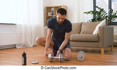 man assembling dumbbells at home - fitness, sport,...