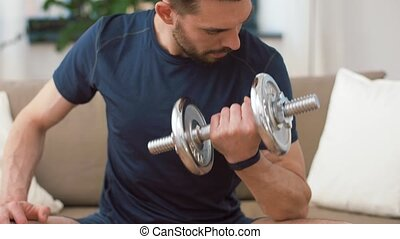 man exercising with dumbbells at home - fitness, sport,...
