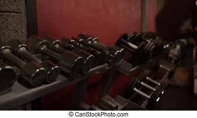 man taking dumbbells from storage rack in gym