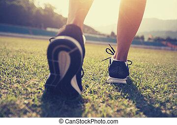 Fitness sportswoman legs running on stadium grass