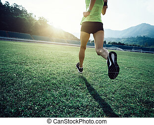 Fitness sportswoman running on stadium grass
